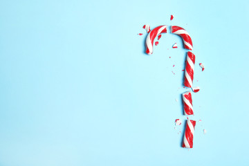 Broken candy cane and space for text on color background, top view