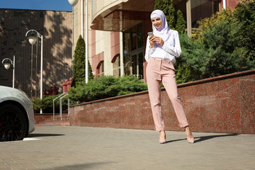 Muslim woman in hijab with mobile phone outdoors