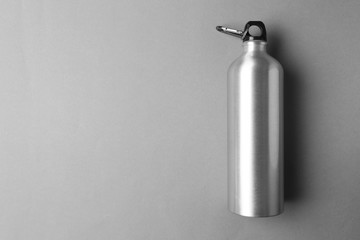 Sport bottle with space for text on color background, top view