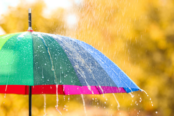 Bright color umbrella under rain outdoors, closeup