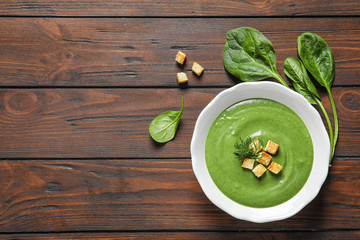 Flat lay composition with fresh vegetable detox soup made of spinach in dish and space for text on wooden background