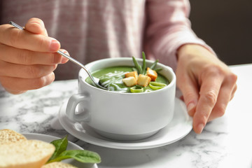 Woman eating fresh vegetable detox soup with croutons at table, closeup