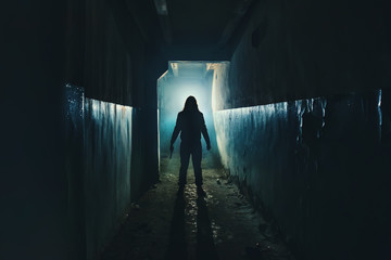 Silhouette of man maniac or killer or horror murderer with knife in hand in dark creepy and spooky corridor. Criminal robber or rapist concept in thriller atmosphere