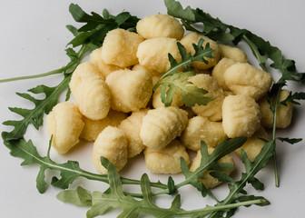 Uncooked raw gnocchi with arugula