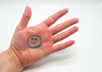 Caucasian female hand with a blue smiley face drawn in the palm isolated on white