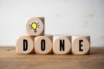 "cubes with the word ""done"" and an idea symbol on wooden background"