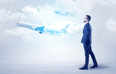 Elegant businessman going somewhere with briefcase and airplane on the background