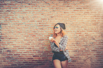 Happy young woman standing against brick wall.