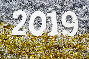 Happy New Year 2019 wooden number on shiny tinsel background