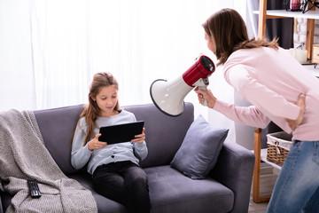 Mother Shouting Through Megaphone At Girl Using Digital Tablet