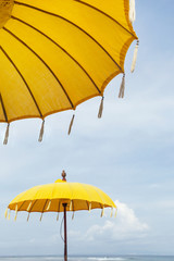 Yellow color umbrella under the blue sky on the beach, close-up photo