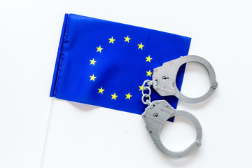 Violation of law, law-breaking concept. Metal handcuffs on European flag on white background top view
