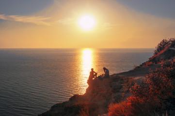 Пара туристов сидят на краю обрыва скалистого побережья Черного моря на закате солнца. Мыс Фиолент, Крымский полуостров