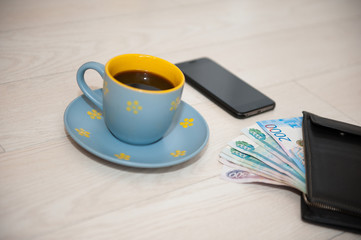 A Cup of coffee, a wallet and a cell phone lie on a wooden stand.
