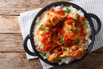 HaitianStewedChicken(Poule en Sauce)served with white rice in a black pan closeup. Horizontal top view