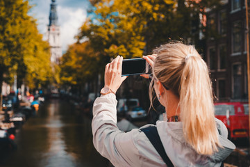 Woman tourist taking a picture of canal in Amsterdam on the mobile phone. Warm gold afternoon sunlight. Travel in Europe