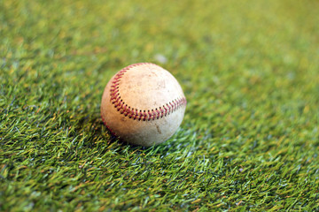 Old baseball on grass background