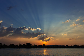 sunset over the river with clouds, light rays and reflection on the water