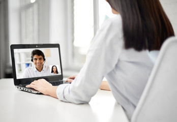 business, technology and communication concept - close up of businesswoman with laptop computer having video call with partner or customer service operator at office