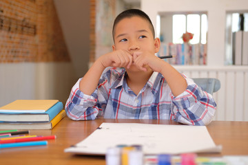 asian kid boy child schoolboy thinking while drawing picture. children activity at home
