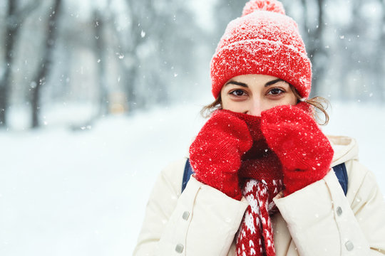 closeup portrait of a smiling woman in warm clothes, red knitted cap, scarf and mittens walking on the snowy street under falling snowflakes after blizzard in city. Happy woman playing with the snow