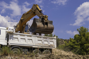 Yellow excavator on the construction site loads the soil into the body of a white dump truck