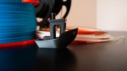 Fototapeta One black 3D printed boat with 3D printer filament on a black background. obraz