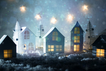 Christmas magic background with little decorative houses, beautiful festive still life, cute small houses at night, happy winter holidays. Selective focus