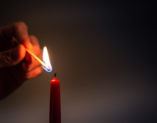 Close up of hand lighting red candle with match