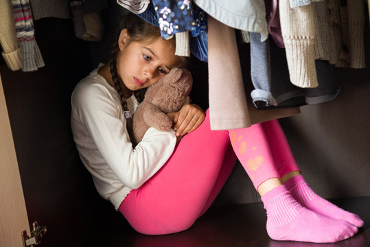 Domestic violence and abused concept. Sad and scared child hiding in the wardrobe and sitting there down in the mouth with Teddy in her hands