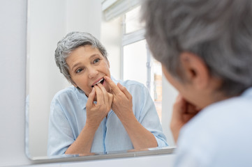 Mature woman cleaning teeth with floss