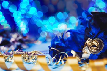 Traditional female carnival venetian mask on blue bokeh background. Masquerade, Venice, Mardi Gras, Brazil festival concept