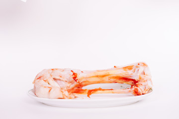 on a white plate on a plate lies a fresh chicken leg in the blood