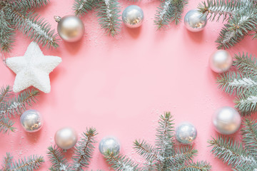 Christmas frame made of fir branches, snowy white decorations,white star balls on pink table. Xmas background. Flat lay. Top view with copy space