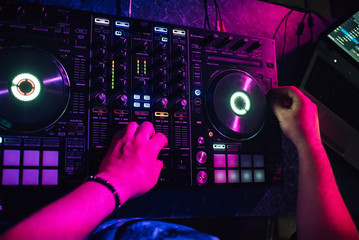 DJ plays with his hands on a music mixer in a nightclub