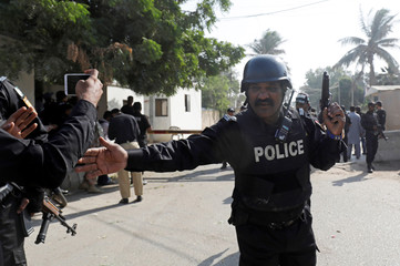 A Police officer stops people which take pictures with their cell phones, after an attack on the Chinese consulate, in Karachi