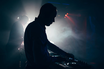 DJ with headphones performs at a music concert in a nightclub