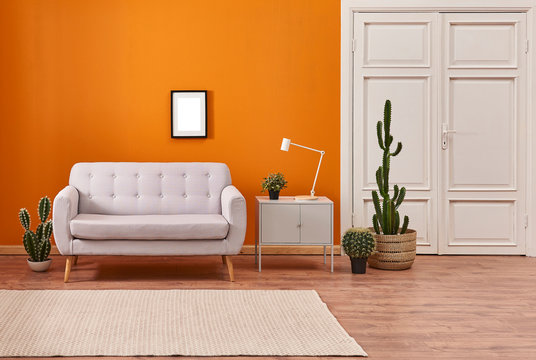 Orange living room, sofa and cupboard, white lamp with many cactus style with carpet.