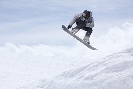 Snowboarder flying on the background of snowy slope. Extreme winter sports, snowboarding. Copy space.