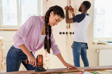 selective focus of african american woman working with jigsaw while her boyfriend standing behind during renovation at home