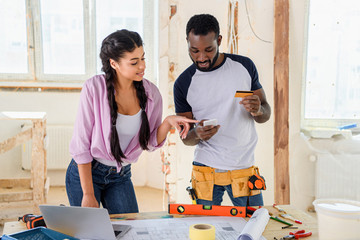 happy young couple making e-shopping during renovation of home