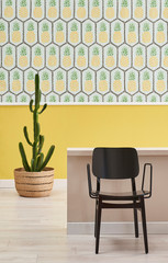 Pineapple wallpaper, yellow wall and close up black chair.
