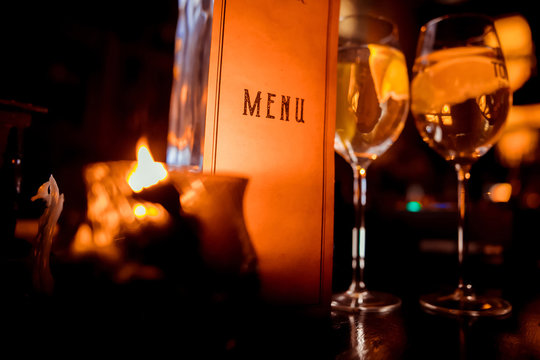 restaurant menu on the background of glasses with wine and candles
