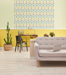 Home office style, yellow wall pineapple wallpaper and work desk style, sofa and laptop.