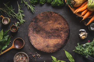 Food cooking and healthy eating background with round wooden cutting board and fresh seasoning, spoon and vegetables, top view, frame. Copy space for your text and design Wall mural