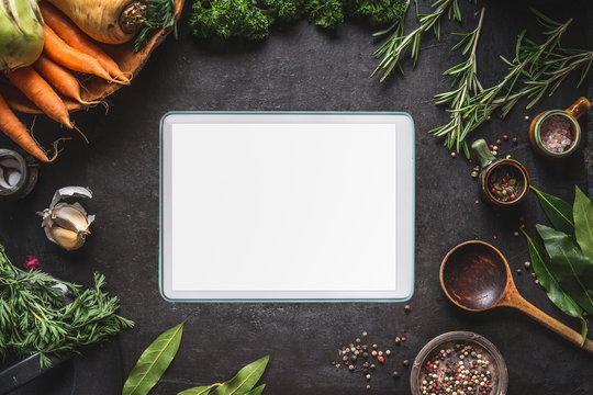 Food cooking and healthy eating background with  tablet pc with empty white screen. Fresh seasoning, spoon and vegetables ingredients, top view. Copy space for your text and design