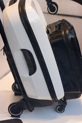 Small suitcase is attached to a larger suitcase on wheels. Vertical image. Concept: travel.