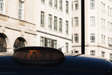 Image of black taxi car on a city street among high buildings. Concept: urban transport & travel.