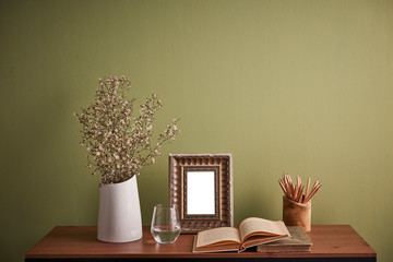 wooden table vase of flower frame book and green wall.