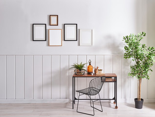 Frame on the wall, modern wooden desk and metal chair with vase of green plant.